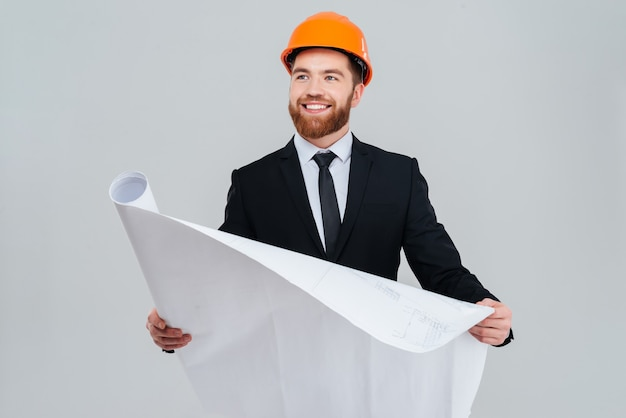 Bearded happy engineer in black suit and orange helmet with open layout looking aside.