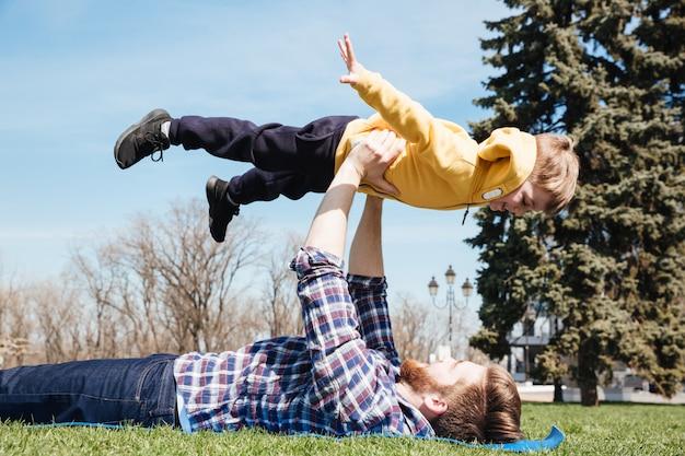 Padre felice barbuto divertendosi all'aperto con il suo piccolo figlio