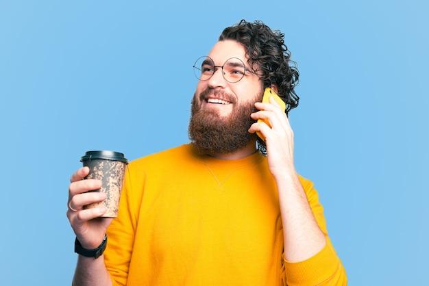 一杯のコーヒーを保持し、電話で話しているひげを生やした幸せな流行に敏感な男