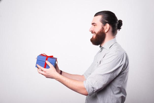 수염 난 행복한 사람이 누군가에게 선물을 주려고 선물을 들고있다.