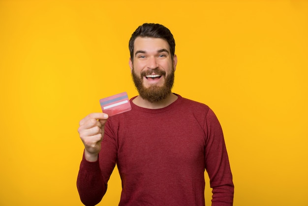 Bearded happy man in red sweater is holding a credit card near yellow background.