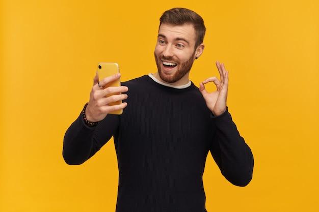 갈색 머리를 가진 수염, 행복한 남자. 피어싱이 있습니다. 검은 스웨터를 입고. 괜찮아요, 괜찮아요. 셀카 만들기. 화상 통화가 있습니다. 노란색 벽에 고립 된 그의 전화를보고