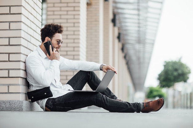 A bearded, happy, smiling, stylish man sitting on the flour on the streets of the city near modern office centre and workin with his laptop and calling phone