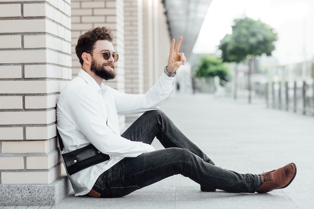 A bearded, happy, smiling, stylish man sitting on the flour in white shirt greetings with friends on the streets of the city near modern office centre