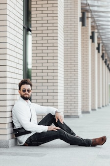 A bearded, happy, smiling, stylish man sitting on the flour in white shirt on the streets of the city near modern office centre