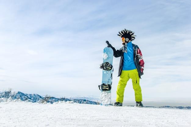 Бородатый счастливый сноубордист в лыжной маске с очками и меховой шапке большой ирокез на фоне неба