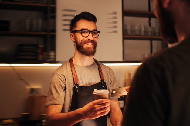 Bearded hipster barmen that wears glasses standing behind the bar stand and holding a cup of coffe that he did for the customeer. the barman looks happy and smiling.