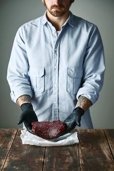Бородатый хипстер-мясник в черных перчатках предлагает кусок стейка из китового мяса