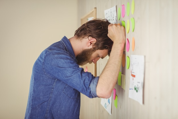 Bearded hipster frustrated at brainstorm wall