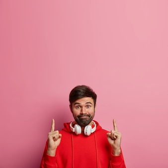 Bearded hipster guy points both index fingers above, shows amazing blank space, gives nice offer, presses lips, wears stereo headphones and red hoodie isolated on pink pastel wall. look upwards
