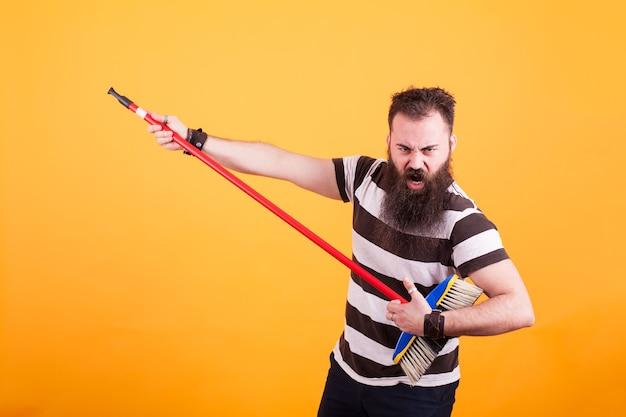 줄무늬 티셔츠를 입은 수염 난 힙스터는 노란색 배경 위에 기타인 것처럼 빗자루를 사용합니다. 쿨한 남자.,