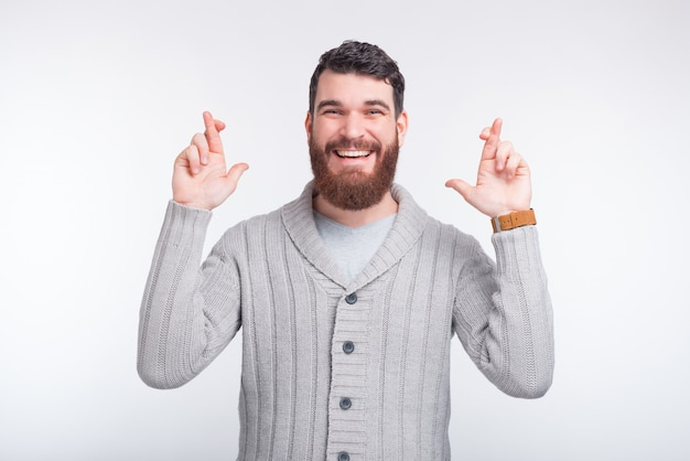 Bearded hipster is crossing fingers hoping for something.