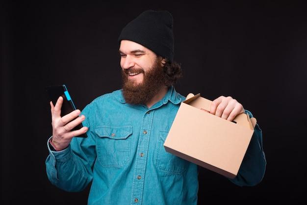 あごひげを生やしたヒップスターは、お弁当と彼のタブレットを持っています。