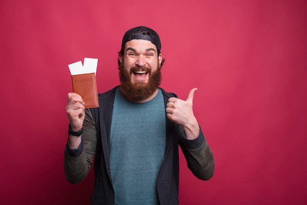 Bearded hipster is showing thumb up while holding his passport with tickets