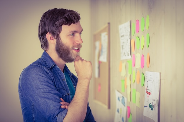 Bearded hipster looking at brainstorm wall