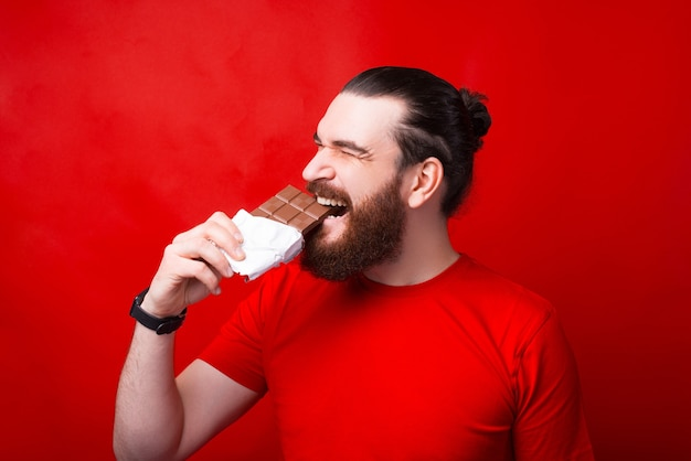 Bearded hipster man eating tasty bar of chocolate over red wall
