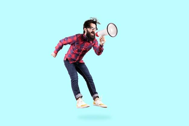 Бородатый хипстерский мужчина в очках, прыгает и кричит в мегафон, фото на синем фоне