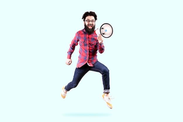 Бородатый хипстерский мужчина в очках, прыгает и кричит в мегафон, фото на синей стене