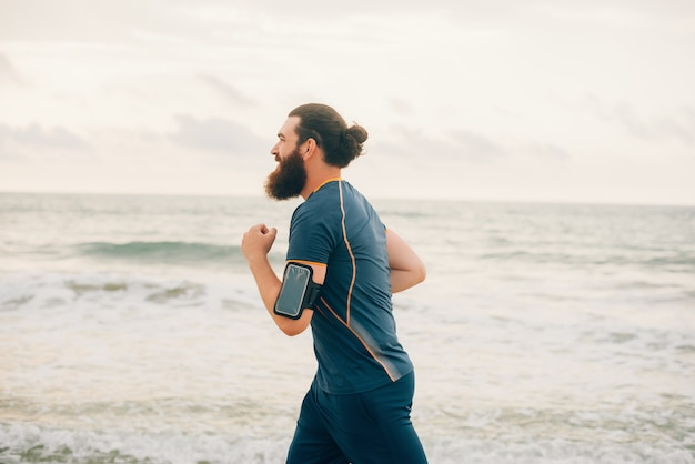 曇りの日に海や海の近くのビーチでひげを生やした流行に敏感な男が走っています。