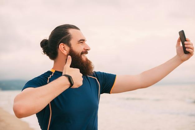 ひげを生やした流行に敏感な男がビーチを走った後、自分撮りをしています。