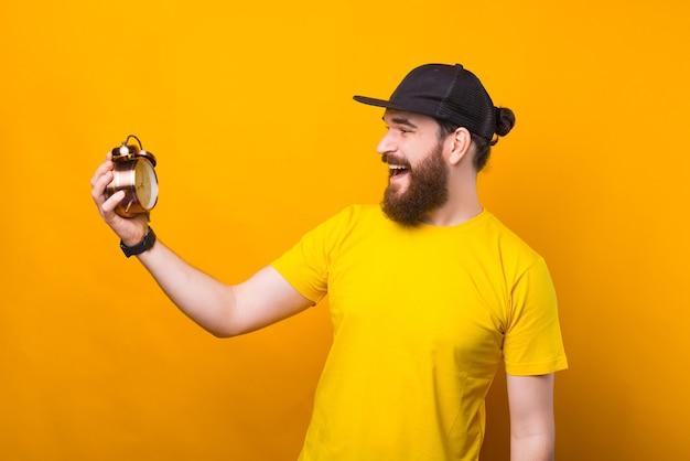 黄色の目覚まし時計を見ているひげを生やした流行に敏感な男