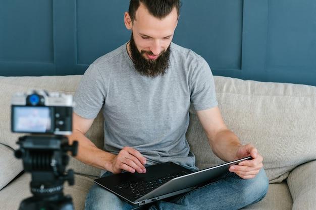 ラップトップを保持しているカメラの前に座っているひげを生やしたヒップスターの男。ライブビデオストリーミングとソーシャルネットワークのビジネストレンドの概念。