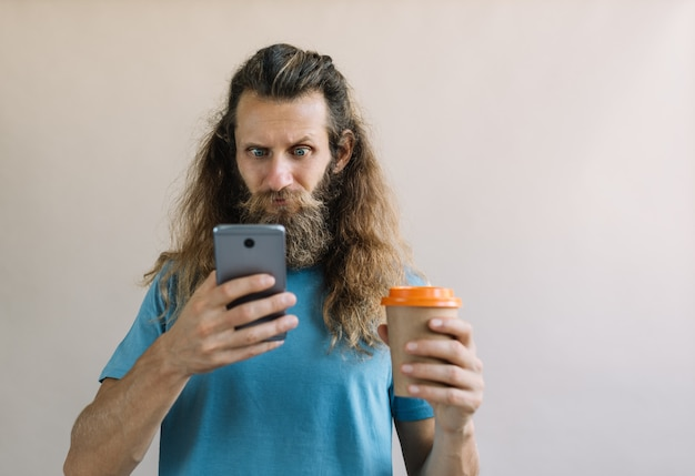 Bearded hipster man using smartphone with mobile app for searching barbershop, he needs beard shaping and hair cutting