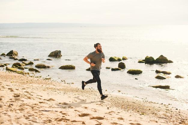 スポーツウェアを着たひげを生やした流行に敏感な男性が朝のビーチを走っています。