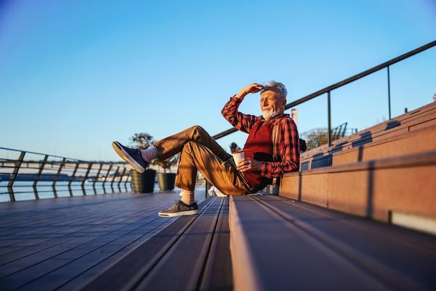 Бородатый битник старший мужчина сидит на лестнице на открытом воздухе, пьет кофе и смотрит на реку.