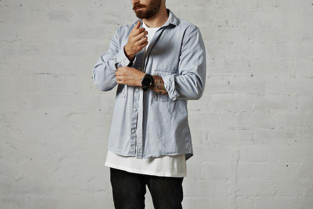 ひげを生やしたヒップスターがボタンを外し、白い壁のカジュアルな色あせた青いデニムシャツの2番目の袖を巻き上げます