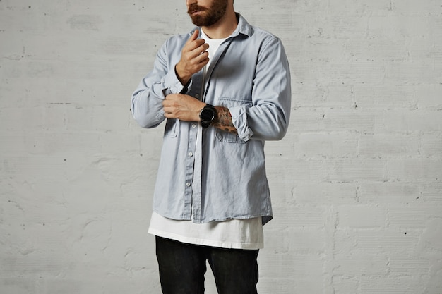 Bearded hipster unbuttoning and rolling up the second sleeve of his casual faded blue denim shirt with white walls