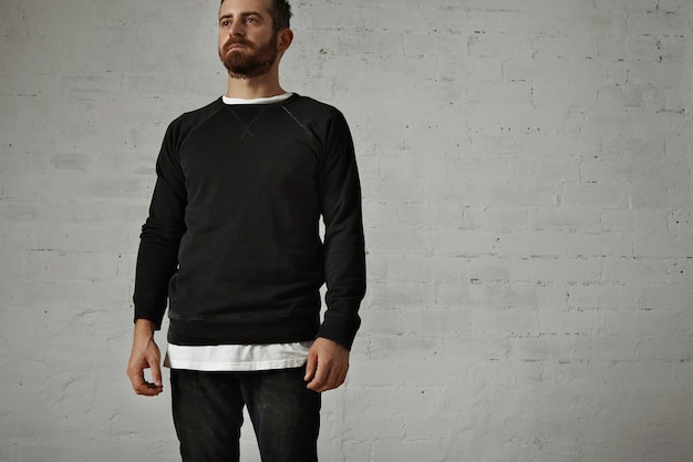 Bearded hipster wearing a blank black longsleeve shirt with a white t-shirt underneath and black jeans on white brick wall