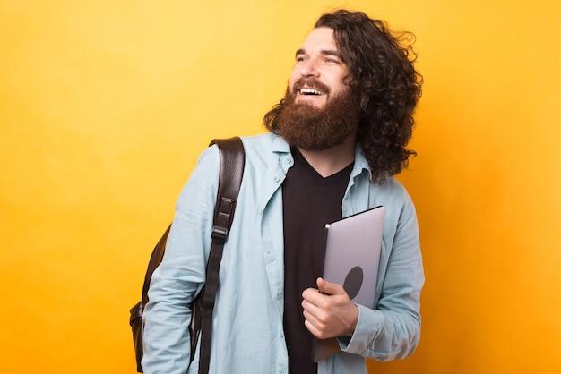 Бородатый хипстер с длинными волнистыми волосами держит ноутбук и носит рюкзак.