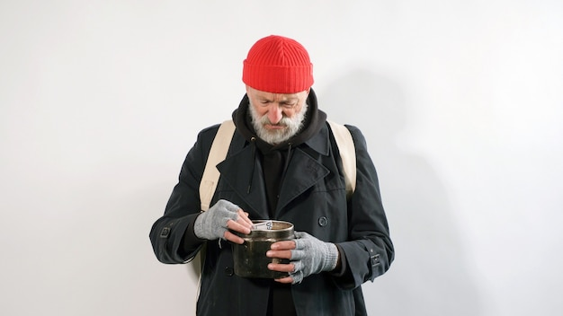 Bearded, homeless beggar old man, in a coat and hat without money on an isolated white background
