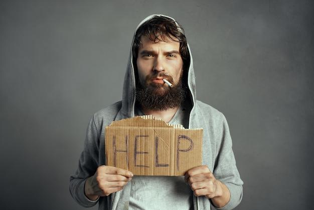 표지판을 들고 수염난 노숙자는 거리에서 감정 빈곤을 돕습니다.