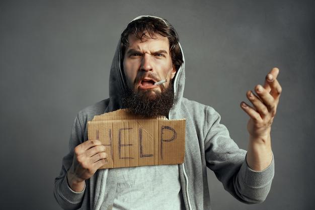 看板を持っているひげを生やしたホームレスの男性は、路上での感情の貧困を助けます