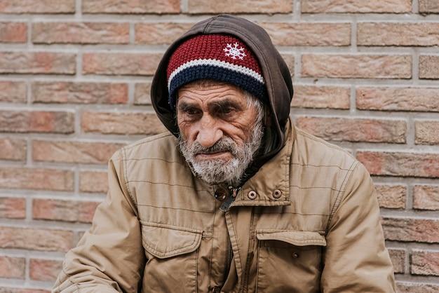 Бородатый бездомный перед кирпичной стеной