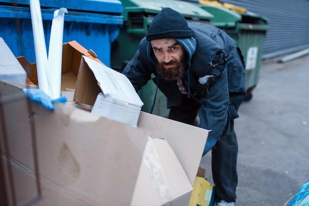 街の通りのゴミ箱で食べ物を探しているひげを生やしたホームレス。