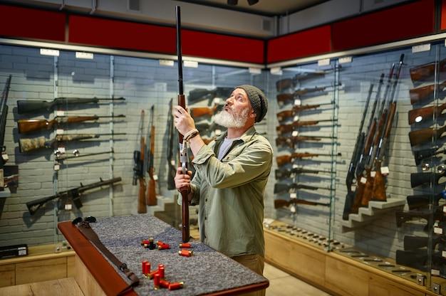 Бородатый охотник покупает охотничье ружье в оружейном магазине