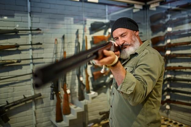 Бородатый охотник выбирает охотничье ружье в оружейном магазине
