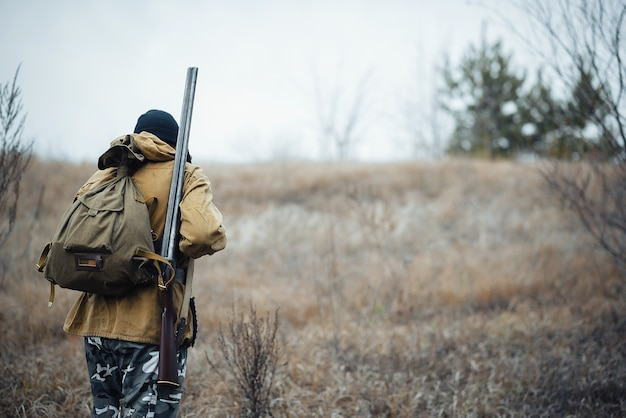 A bearded hunter man in a dark warm hat in a khaki jacket and camouflage pants with a gun on his shoulder