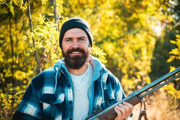 銃を持って森の中を歩くひげを生やしたハンター男。狩りに散弾銃銃を持ったハンター。春の森での狩猟。
