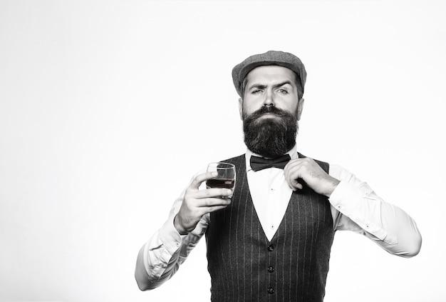あごひげを生やしたのはウイスキーのグラスを持っています。ソムリエは高価な飲み物を味わいます。飲み物のガラスとジャケットのハンサムな身なりのよい男。スーツを着てウイスキー、ブランデー、コニャックを飲むひげを生やした男。