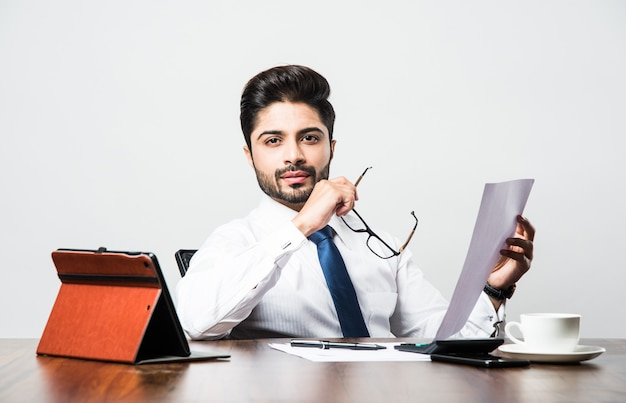 사무실에서 책상 테이블에 앉아있는 동안 수염된 인도 사업가 회계
