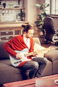 あごひげを生やした楽器奏者。ソファに座って家でギターを弾くひげを生やした黒髪の楽器奏者
