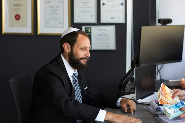 키파에 있는 수염난 유태인 남자는 많은 현금으로 사무실에 앉아 있습니다. 은행 대출 또는 신용. 몇 분 안에 현금을 받으세요. 은행 지원 라인 개념입니다. 이스라엘 돈, 새 세겔 지폐를 세는 여자
