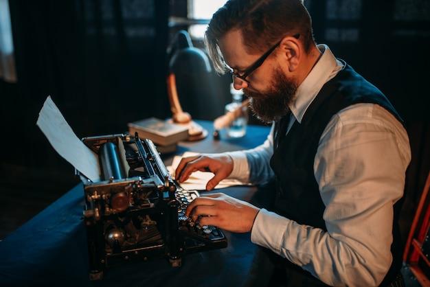Бородатый журналист в очках печатает на пишущей машинке