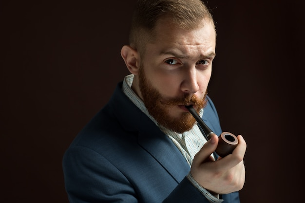 Bearded lamber like male model in suit with moustache and beard smoking pipe