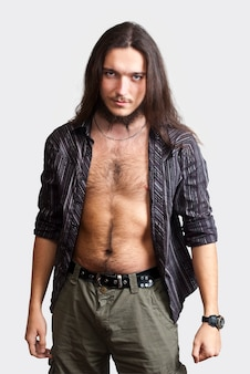 수염이 긴 머리 젊은 남자가 속박 셔츠를 입고있다