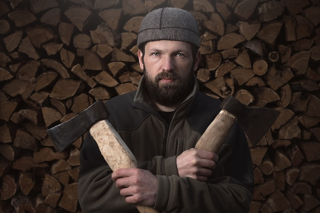 Bearded lumberjack in front of firewood log. country life.
